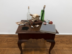 Merik Goma  Memento Mori, 2019  Table, books, paints, plastic skull, flower crown, glass  Installed dimensions variable