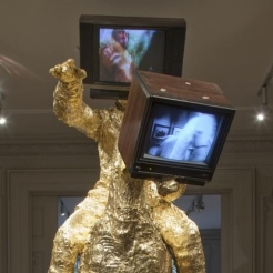 Gold leaf sculpture of a man on a horse with both heads replaced with televisions by The Bruce High Quality Foundation