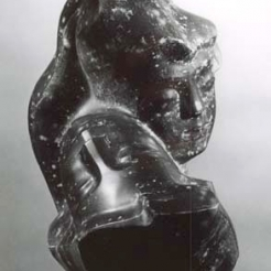 Metal sculpture of two intertwined female heads with serene expressions on their faces. Both of the heads have specks of white dots on them.