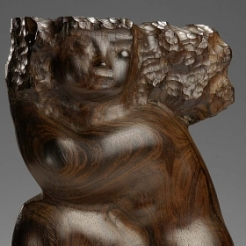 Rosewood sculpture of a crouched, sitting woman. Her head is cradled into her right bent elbow which rests on her knee while her other leg is tucked behind. Her hair flies back from her head, featuring pock mark textured detailing.
