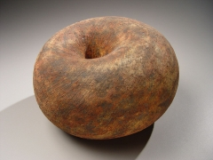 Round sculpture with concave center and rough texture of deep red and black slip glaze, 2007