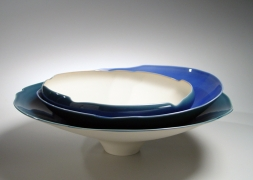 Low round porcelain form of three blue-glazed bowls stacked unevenly inside one another, with center oculus of overlapping bowls, 2012