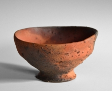 Koyama Fujio (1900-1975), Brick red rounded and slightly tilted teabowl with black speckles, oval mouth,bachikōdai(flared foot rim), and smoke-infused kiln effects made from Tanegashima clay