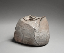 Kaneta Masanao (b. 1953), Covered water storage jar with multi-plane body, unctuous Hagi and natural ash glazes, kiln effects and matching lid with knob handle