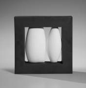 Itabashi Hiromi, Wall hanging sculpture comprised two ovoid white unglazed porcelain vessel-like elements encased in black, metallic glazed thick framework, titled Association with White
