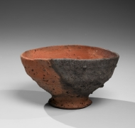 Koyama Fujio (1900-1975), Brick red rounded and slightly tilted teabowl with black speckles, oval mouth, bachikōdai (flared foot rim), and smoke-infused kiln effects made from Tanegashima clay