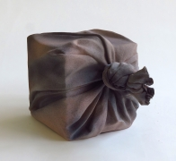 Brown and black sculpture in the shape of furoshiki (wrapping cloth) wrapping a square box, 2017