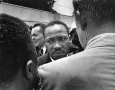Martin Luther King Jr., who led the procession of mourners at the funeral of Medgar Evers, is confronted by a Mississippi Highway Patrol Officer, 1963, Archival Pigment Print
