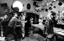 Blake Edwards throwing a pie at Natalie Wood on the set of The Great Race, Warner Bros. Studio, Burbank, California, 1964