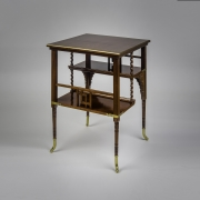 """""""Tiered Table in the Aesthetic Taste,"""" about 1880. A. & H. Lejambre (active 1865–1907), Philadelphia. Mahogany, with inlays of brass, copper, and pewter, and brass moldings, straps and sabots, 27 in. high, 20 in. wide, 20 in. deep,"""