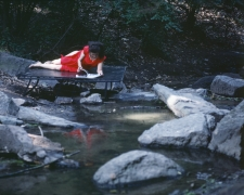 Rivers, First Draft: The Woman in Red, on a bed jutting into the water, skims an accordion-folded album of photos, 1982/2015, Digital C-print in 48 parts,16h x 20w in (40.64h x 50.80w cm)