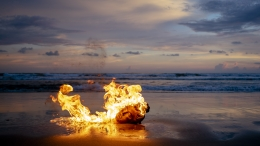Flaming Quanyin head on a beach at night