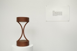 , IMAN ISSA Laboring (Study for 2012), 2012 Mahogany sculpture, text panel under glass, and white plinth Overall: 53 x 11 12 in. (134.62 x 29.21 cm) Text panel: 11 x 17 in. (27.94 x 43.18 cm) Edition of 4 Courtesy Rodeo Gallery