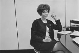 Secretary smoking at her desk, Detroit, 1968