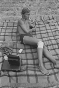 Man with injured knee at the beach smoking, Detroit, 1968