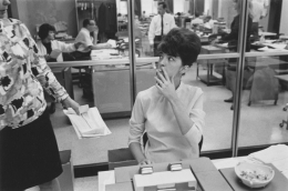 Secretary smoking at her desk, Detroit, 1968
