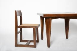 Close up view of Pierre Jeanneret's square table shown with a Jeanneret chair