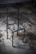 Michele Oka Doner's Terrible Chair, full diagonal view from above in a darker warehouse setting