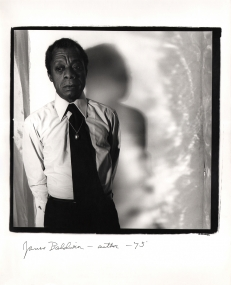 Anthony Barboza, James Baldwin - Author, ​1975. Subject stands to the left of square frame with his shadow cast to the right onto the backdrop.