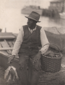 Doris Ulmann, Untitled (Fisherman),  ​1928–1934. Man seated on the bow of a small fishing boat holding a basket and fish.