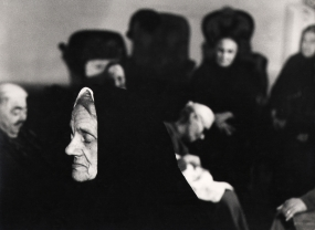 Mario Giacomelli, Verrà la morte e avrà i tuoi occhi, 1966–1968. High contrast image. A cloaked woman in the foreground with closed eyes, facing the left of the frame. Various figures out of focus behind her.