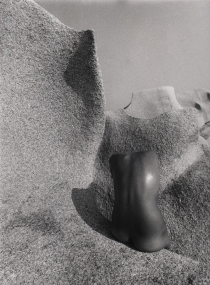 Pino Dal Gal, Capo Testa (Sardinia), ​1977. Abstracted nude torso photographed from behind against a stone landscape.