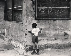 20. Beuford Smith, Playing 'Hide and Seek,' ​1968. A young boy stands against the corner of a run-down building.