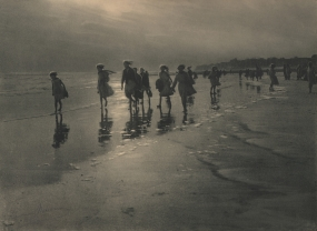 Léonard Misonne, La brise, 1926. A group of girls walk along the beach with bare feet in the water. Gray/green-toned print.