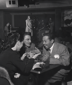 Wayne F. Miller, Billy Eckstine, ​1948. Subject is seated, smiling, at a club table with two other figures. A woman sings on stage in the background.