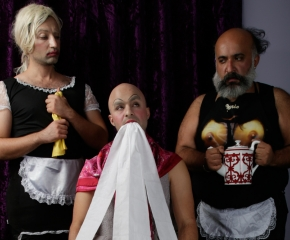 A film still of 3 men, two of whom are dressed like maids