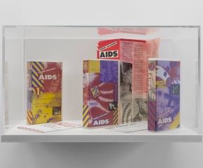 """A vitrine that contains 2 tapes and a program for the """"Video Against AIDS"""" program"""