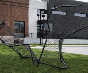 Black chain link fence sculpture jutting out of grass
