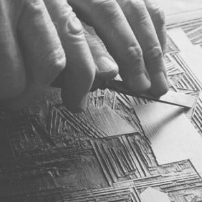 Lyonel Feininger carving a woodblock.