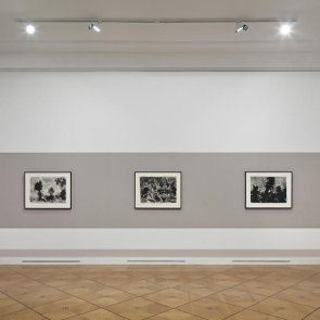 Three works by Mark Tobey hung on a gray wall.