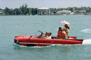 """Slim Aarons, Sea Drive: Film producer Kevin McClory takes his wife Bobo Segrist and their family for a drive in an """"Amphicar"""" across the harbour at Nassau, Bahamas, 1967"""