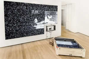 An image of Survivor's Remorse, a video installation with one flat-screen in a grid of 9 flatscreens on the ground in an open crate
