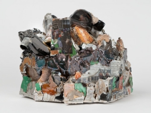 A mixed clay sculpture with black and green lusters, decals, and digital images