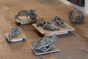 A gathering of bronze sculptures on small wooden pedestals