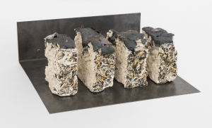 A mixed media clay sculpture with decals of cigarettes upon them