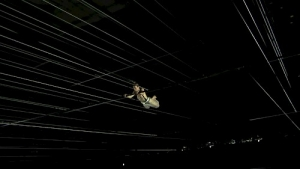A photograph of a dark room and a person swinging from trapeze in the center of the picture