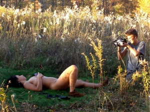 A photograph of a naked woman in a field being videotaped at right
