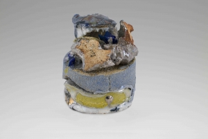 A small multicolor stone sculpture with blue, green, and orange tones, silver luster