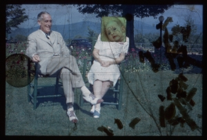 A film still of 2 elderly white people sitting on chairs on the grass. There are appliques and an image over the woman's face