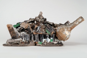 A mixed media clay sculpture with a vessel at right, green and black luster, and newspaper decals