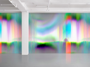 "An installation image of James Hoff's ""Skywiper 122,"" a vinyl wallpaper made up of bright green, orange, purple, blue striations and glitches"