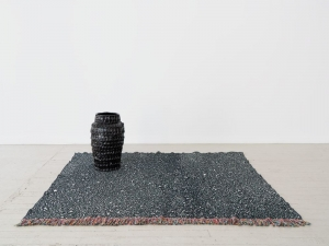 A black sculpture on a black and white jacquard rug