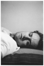 A black and white portrait of Guibert laying on a bed