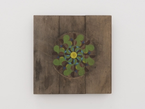 A pinwheel shape painted in green and purple on a square panel of wood