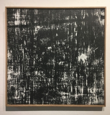 An abstract work of striations with black and white, in a wood frame