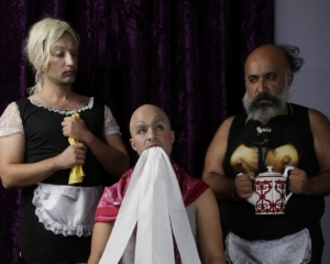 A freeze-frame of a film work. The image depicts the three artists. At left, the artist is dressed as a traditional french maid. The figure in the middle holds toilet paper in his mouth. The figure at right is wearing a french maid bib with a t-shirt.